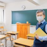 asian senior male professor wearing face mask hold books and look at you in front of blackboard at college classroom
